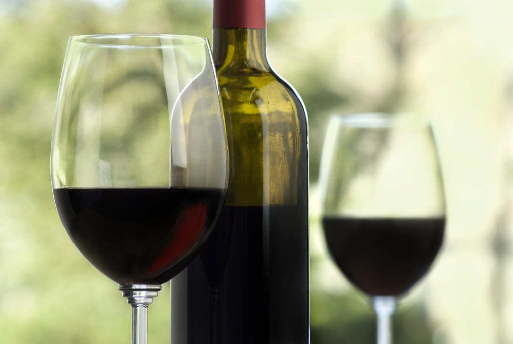 close up of wine glass, red glow visible, bottle and second glass soft focus in background, outdoors